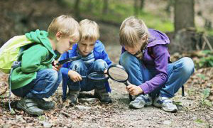 Children using magnifying glasses at Riverbank Discovery Centre, Brandon, Manitoba